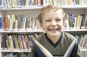 smiling-little-boy-holding-book-in-library-uid